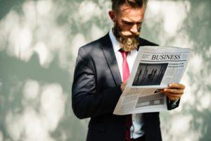 foto van man in pak die staand een krant leest